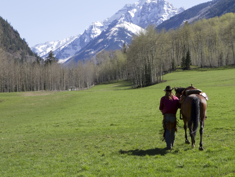 Colorado landscape with woman walking horse in field with mountains in background