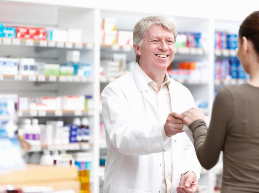 Pharmacist handing prescription to patient